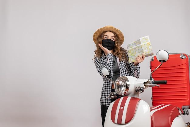Ładna młoda dziewczyna z maską trzymająca mapę stojącą w pobliżu motoroweru