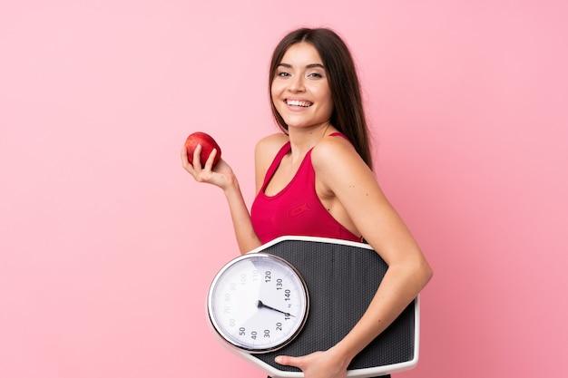Ładna młoda dziewczyna z ważyć maszynę nad odosobnioną menchii ścianą z ważyć maszynę z jabłkiem i