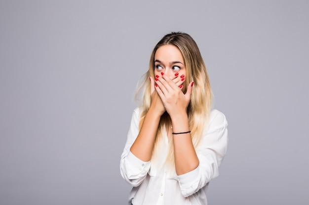 Ładna, młoda dziewczyna zakrywając usta na szarej ścianie