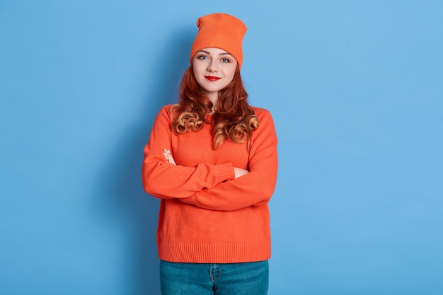 Ładna młoda europejka jest spokojna, ma założone ręce, nosi pomarańczowy sweter i czapkę