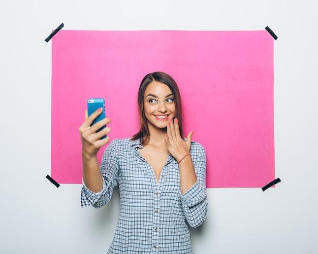 Ładna młoda kobieta bierze obrazek z kamera telefonem