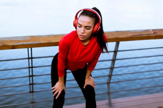 Ładna młoda kobieta bierze przerwę po biegać
