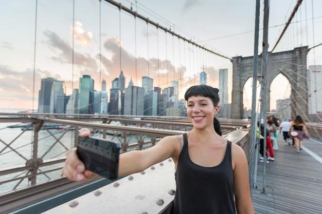 Ładna młoda kobieta bierze selfie na brooklyn moscie