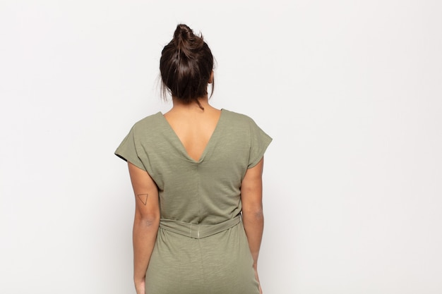 Ładna młoda kobieta czuje się zagubiona lub pełna lub ma wątpliwości i pytania, zastanawiając się, z rękami na biodrach, widok z tyłu