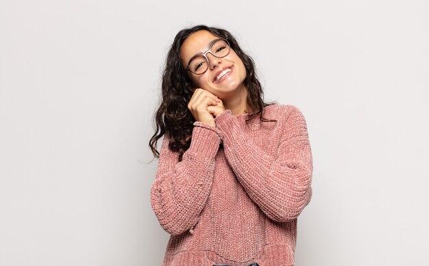 Ładna młoda kobieta czuje się zakochana i wygląda uroczo, uroczo i szczęśliwie, romantycznie uśmiechając się z rękami obok twarzy