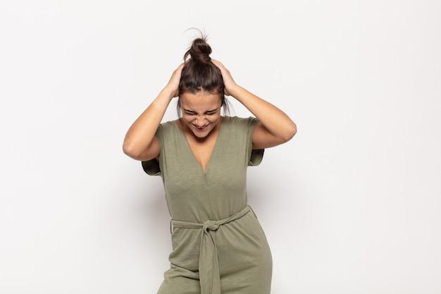 Ładna młoda kobieta czuje się zestresowana i sfrustrowana, podnosi ręce do głowy, czuje się zmęczona, nieszczęśliwa i ma migrenę