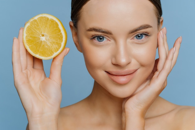 Ładna młoda kobieta delikatnie dotyka twarzy ma zadbaną cerę zdrową, promienną skórę