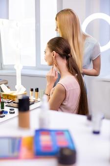 Ładna młoda kobieta dotyka swoich nowych kolczyków, patrząc na swoje odbicie w lustrze