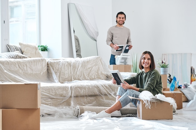 Ładna młoda kobieta i jej mąż patrzą na ciebie w ramkach do zdjęć podczas rozpakowywania pudeł w swoim nowym domu