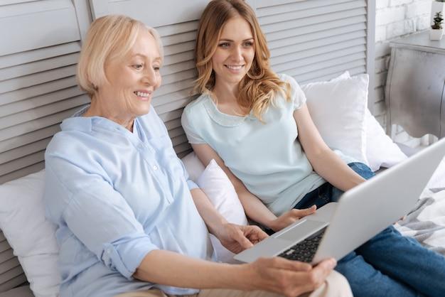 Ładna młoda kobieta i jej urocza starsza matka siedzą na łóżku, trzymając laptopa i oglądając na nim coś przyjemnego