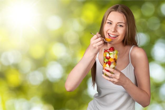 Ładna młoda kobieta je sałatkę owocową na tle