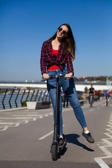 Ładna młoda kobieta jedzie elektryczną hulajnoga na ulicie