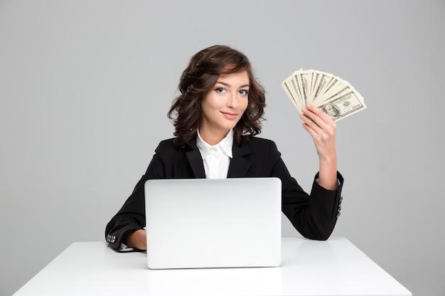 Ładna młoda kobieta korzysta z laptopa i pokazuje pieniądze