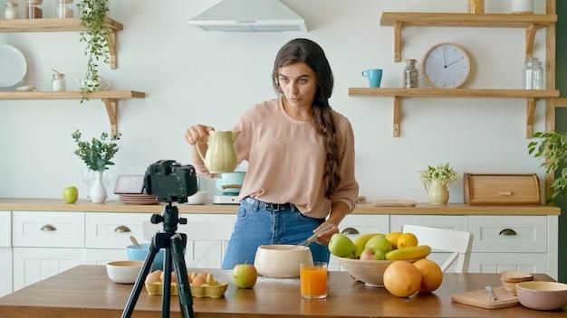 Ładna młoda kobieta kręci bloga o gotowaniu. blog wideo o zdrowej żywności. atrakcyjna kobieta gotuje w aparacie. kobieta transmituje wideo online vlog.dziewczyna prowadzi zdalne nauczanie gotowania