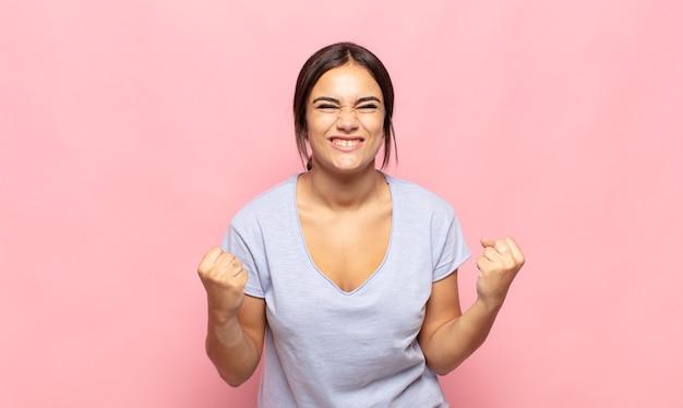 Ładna młoda kobieta krzycząca triumfalnie, śmiejąca się i czująca radość i podekscytowanie podczas świętowania sukcesu
