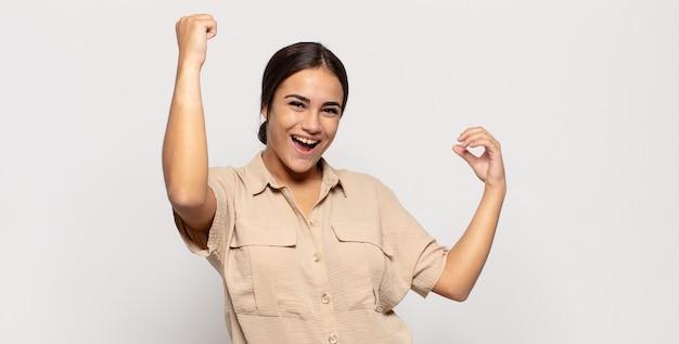 Ładna młoda kobieta krzyczy triumfalnie, wyglądając jak podekscytowany, szczęśliwy i zaskoczony zwycięzca, świętujący