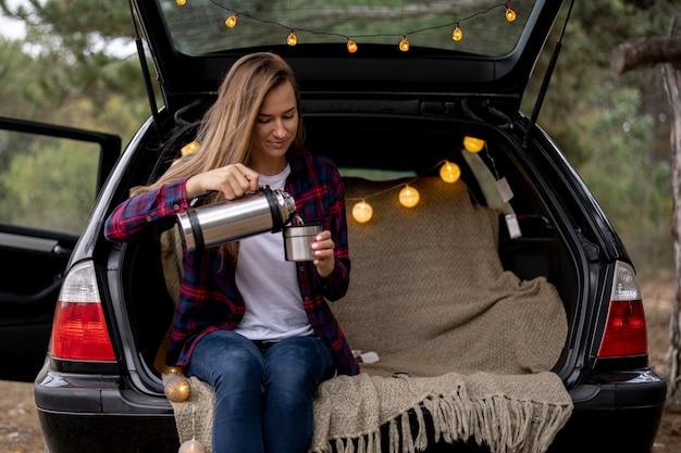 Ładna młoda kobieta leje kawę