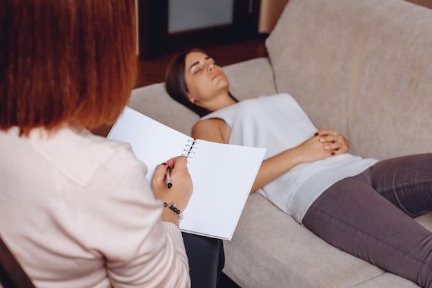 Ładna młoda kobieta, leżąc na kanapie w recepcji z psychoterapeutą. psychiczne problemy psychologiczne. koncepcja problemów psychicznych