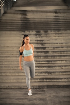 Ładna młoda kobieta ma ćwiczenie w miastowym środowisku