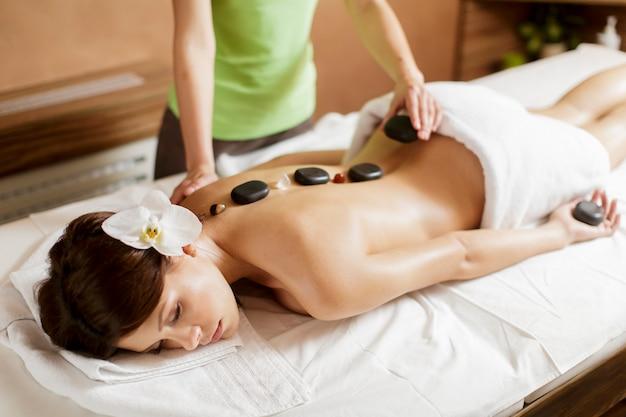 Ładna młoda kobieta ma gorącą kamienną masaż terapię