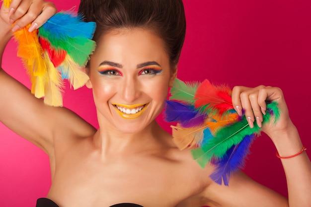 Ładna młoda kobieta na kolorowych tła mienia piórkach. portret atrakcyjna dziewczyna z kreatywnych makijaż