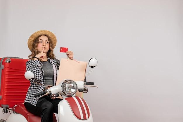 Ładna młoda kobieta na motorowerze trzyma kartę na szaro