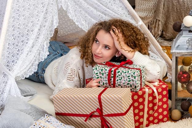 Ładna młoda kobieta na świątecznych pudełkach upominkowych nosi biały sweter z dzianiny