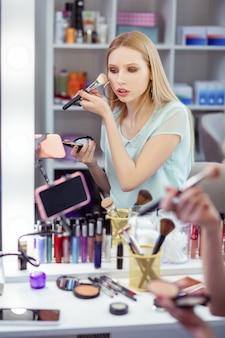 Ładna młoda kobieta nagrywa wideo na swoim smartfonie, jednocześnie prowadząc swój blog kosmetyczny