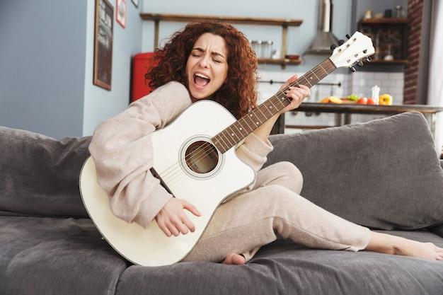 Ładna młoda kobieta nosząca ubrania domowe grająca na gitarze akustycznej, siedząc na kanapie w mieszkaniu