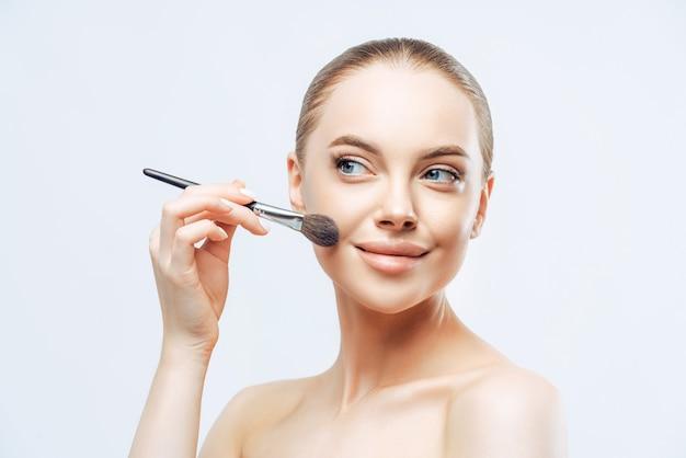 Ładna młoda kobieta o ciemnych czesanych włosach nakłada pudrowy podkład na twarz pędzlem kosmetycznym
