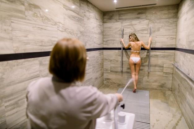 Ładna młoda kobieta o masaż wysokociśnieniowy z prysznicem sharko w nowoczesnym centrum spa. kobieta terapeuta wykonuje zdrój prysznic procedury dla kobiet klienta