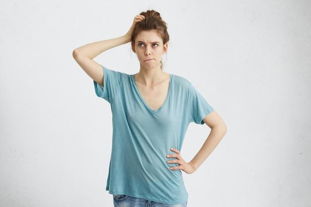 Ładna młoda kobieta o wątpliwym i zamyślonym spojrzeniu, przygryzając usta, planując, co robić dalej. ludzkie myśli