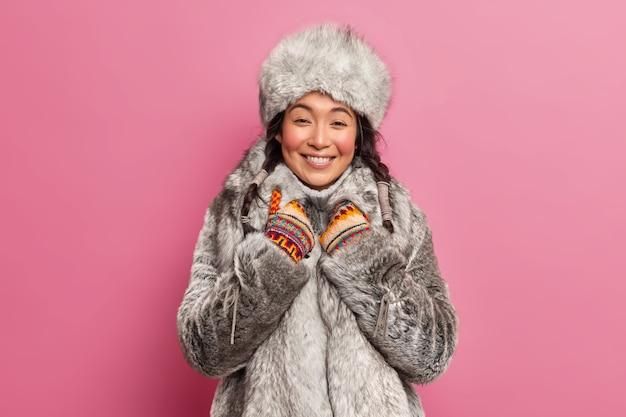 Ładna młoda kobieta o wschodnim wyglądzie, ubrana w szare futro, uśmiecha się szczerze, słyszy coś przyjemnego na zimowy spacer w pozach na różowej ścianie