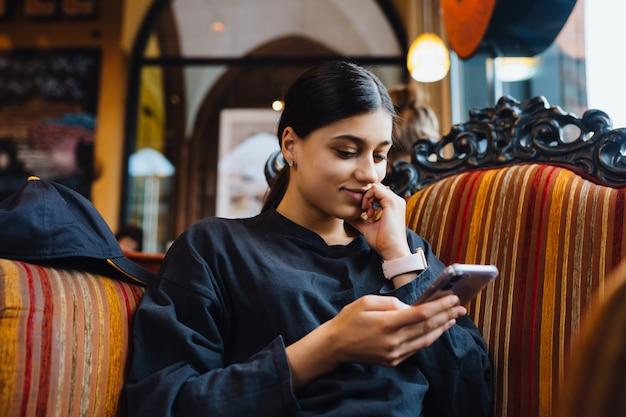 Ładna młoda kobieta odpoczywa na dużym miękkim krześle w kawiarni, gawędzi przez telefon