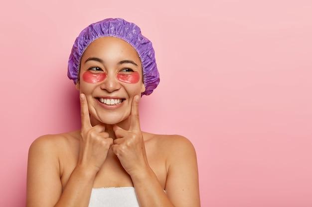 Ładna młoda kobieta owinięta miękkim ręcznikiem, dba o skórę, nosi hydrożelowe plastry regeneracyjne lub kolagenowe płatki, dotyka policzków palcami wskazującymi, nosi czepek kąpielowy, pokazuje odsłonięte ramiona, zdrowa skóra