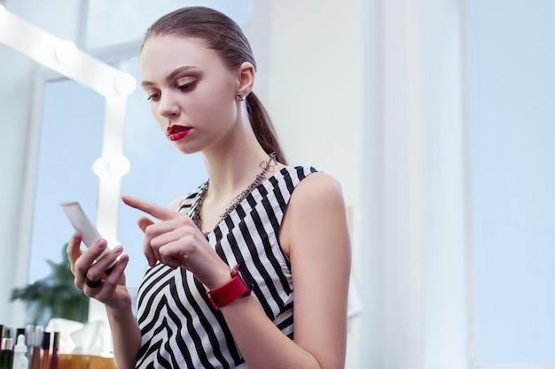 Ładna młoda kobieta patrząca na krem podczas czytania jego składników