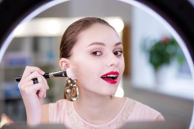 Ładna młoda kobieta patrząca na swoją twarz w lustrze podczas nakładania wieczorowego makijażu