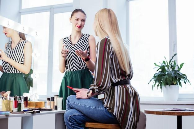 Ładna młoda kobieta patrząca na swojego klienta podczas nakładania makijażu