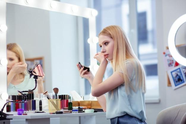 Ładna młoda kobieta patrząca w kamerę podczas nagrywania lekcji makijażu