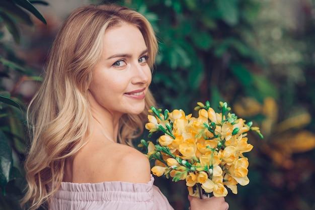 Ładna młoda kobieta patrzeje kamerę trzyma pięknych żółtych kwiaty