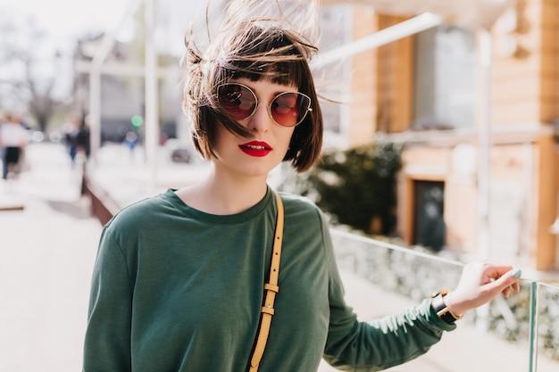 Ładna młoda kobieta patrzeje z zainteresowaniem w okularach przeciwsłonecznych. wspaniała modelka spędzająca wiosenny dzień w mieście.