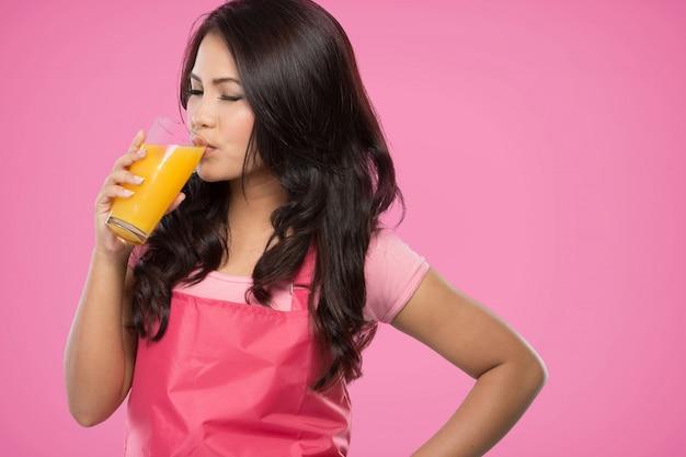 Ładna młoda kobieta pije sok pomarańczowego