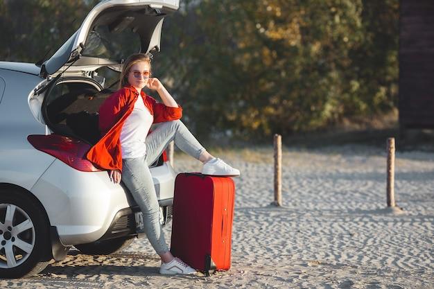 Ładna młoda kobieta podróżuje na samochodzie. kobieta z torby podróżne, siedząc na samochodzie.