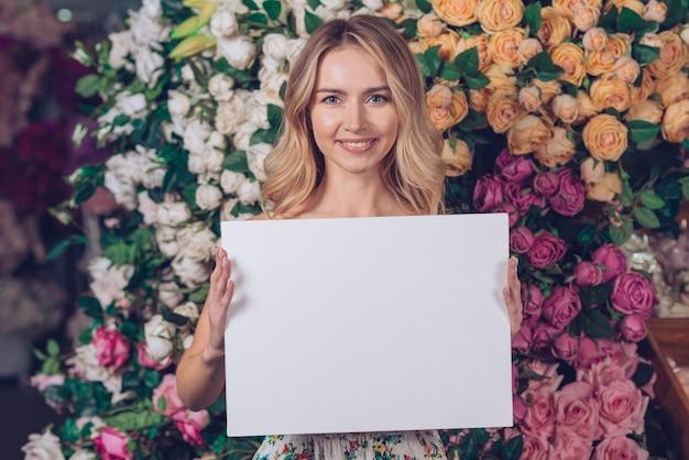 Ładna młoda kobieta pokazuje białego pustego plakat w ręki pozyci przeciw kolorowym różom