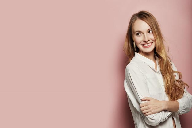 Ładna młoda kobieta pozuje na różowym tle
