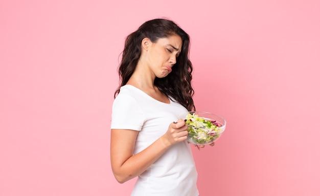 Ładna młoda kobieta przygotowuje sałatkę