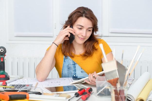 Ładna młoda kobieta robi diy opowiada na telefonie