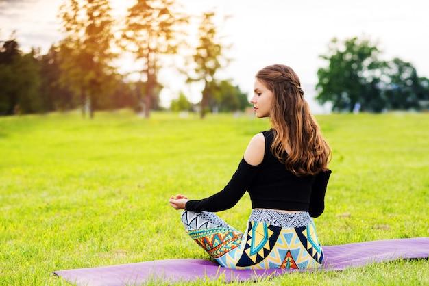 Ładna młoda kobieta robi joga ćwiczy outside w parku na gazonie