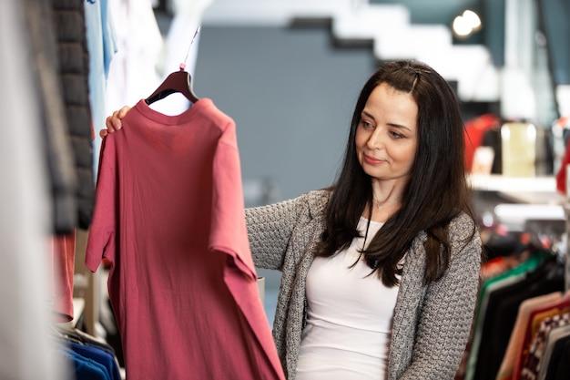 Ładna młoda kobieta robi zakupy lub kupuje ubrania w sklepie lub butiku