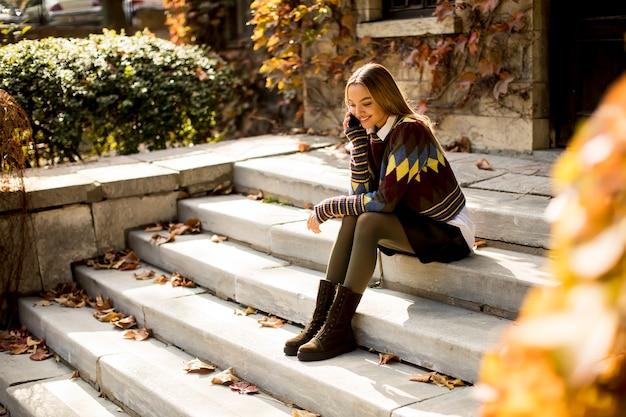 Ładna młoda kobieta siedzi na schodach z telefonem komórkowym w jesiennym parku